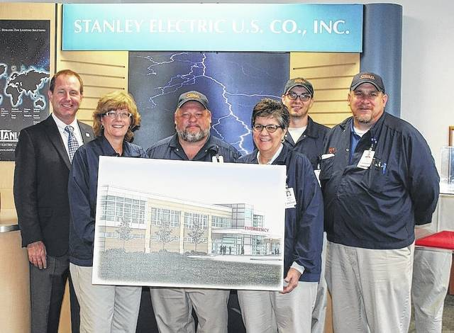 Members of Stanley Electric's Contributions Committee are pictured with company and hospital leaders celebrating Stanley's contribution to the Building on Excellence Campaign. From left are, Dana Engle, Madison Health CEO; Laura Toops, committee member; Brian Boldman, Stanley Executive VP; Cindy Morgan, committee member; Rickey Deere, committee member; and Jim Sollars, Stanley Director. They are holding the artist's rendering of the new addition planned for Madison Health.