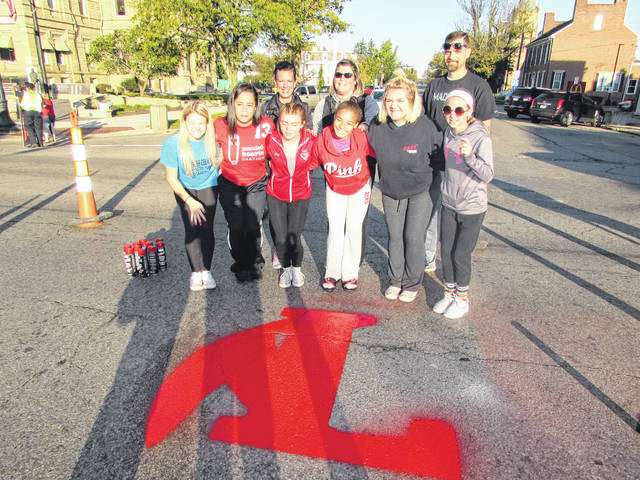"""London High School Junior Varsity Cheerleading Squad members are pictured with the """"Big L"""" London High School emblem after they painted the letter in the center of Main and High Streets Friday morning. Pictured are cheerleaders Chloe Fender, Jayda Cunningham, Denae Doyle, Kylee Long, Hannah Jones, Laney Fisher, Vice President of the London High School Athletic Boosters Stephanie Schooley, cheerleading coach Abby Fisher and Mayor Pat Closser."""