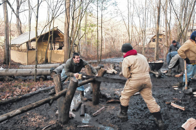 Counselor Randall Wenger of Ohio Boys Camp helps a boy cut firewood for the coming cold weather.