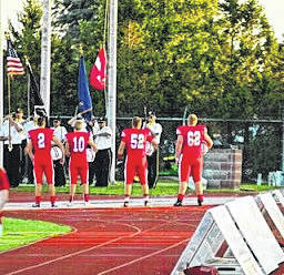 London High School football captains from left: Miller Kronk, Josh Handley, Haden Huff and Jacob Jones stand during the playing of the national anthem prior to the Red Raiders game against visiting Liberty Union Friday.