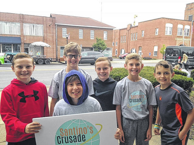 Santino Carnevale, center, and friends soliciting business during a rainy West Jefferson Labor Day parade. From left are: Brett Bogenrife, Zac Thompson, Blake Bogenrife, Ethan Friessan and Caden Bateman.