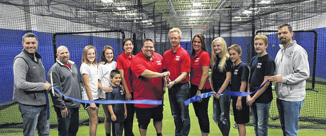 The official ribbon cutting took place for the grand opening of DiamondZ Batting Cages and Indoors Sports Facility on Saturday, Nov. 4. From left are: Madison County Chamber of Commerce Executive Director David Kell, Chamber member Bob Patterson, Natalie Zabloudil, Lexi Zabloudil, Vinny Zabloudil, Owner Renae Zabloudil, Owner Bob Zabloudil, Owner Marvin Homan, Owner Jodi Homan, Abby Homan, Alex Homan, Sam Homan and London Mayor Patrick Closser.