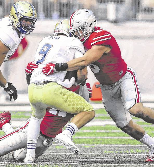 Ohio State Jalyn Holmes (11), left, and Ohio State Sam Hubbard (8) combine to wrap up Tulsa quarterback Dane Evans (9) for a first quarter sack at Ohio Stadium in 2016.