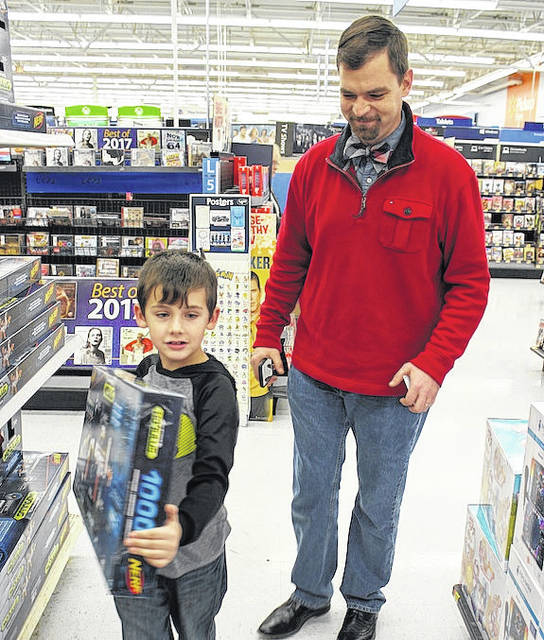 """London Mayor Patrick Closser assists Ryann Harding (7) Monday evening as part of """"Shop With a Cop"""" at Walmart. The event was a coordination of London Police Department and Stacey Jordan of the Department of Jobs and Family Services. Numerous businesses donated goods that were raffled or auctioned off for fundraising for the event."""