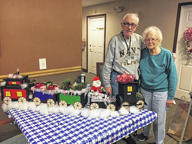 """Jim Weimer (71) and Ruthe Barker (95) display their handmade train set """"Madison Lines"""" at Madison Senior Living Community. The friends spent over a week making the set, using a variety of materials. The train sits under the Christmas tree for all the residents to enjoy."""