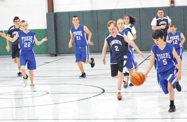 Madison County Tiger Houston Gray dribbles ahead of a crowd of his teammates and opponents from Toledo Public in the local Special Olympics first-annual Holiday Invitational Tournament held at London's Fairhaven School on Dec. 9.
