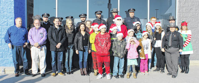 "Officers from the Madison County Sheriff's Department and the West Jefferson Police Department stand with members of the Coughlin family and West Jefferson students Saturday for the village's first ever ""Shop with a Cop"" event. The kids were brought to the Walmart in London to shop with the officers for Christmas."