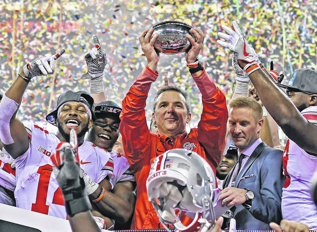 Ohio State coach Urban Meyer hoists the Big Ten Championship trophy following his team's win over Wisconsin Saturday. The Buckeyes did not receive a spot in the College Football Playoff and instead will tangle with USC in the Cotton Bowl.