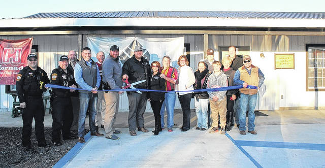 Attending a ribbon cutting ceremony Dec. 20 at Smokin' Aces Armory, 9525 State Route 161, Plain City, are from left: Sergeant Tharon Prather, Plain City Police Department; Detective Philip Greenbaum, Plain City Police Department; Greg Finchum, Re/Max Leading Edge, Madison County Chamber of Commerce board member; David Kell, Executive Director of the Madison County Chamber of Commerce; Tim Suter, Ohio Edison, Madison County Chamber of Commerce board member; Chris Hines, Smokin' Aces Armory; Tyler Lane, Smokin' Aces Armory; Inge Witt, the village of Plain City; Barry Thomas; Linda Granger, the village of Plain City; Traci Tate, Elite FTS, Madison County Chamber of Commerce board member; Jim Hines; Bryce Tate; Rite Hines; Rick Shafer (GraMag) Madison County Chamber of Commerce board member; and Joe Troyer, Plain City Business Association.