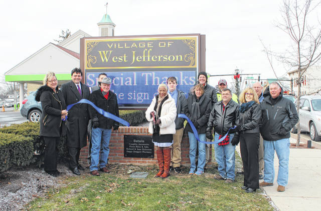 West Jefferson village officials and donors held a ribbon-cutting ceremony for the new digital sign Tuesday. The sign is located on Main Street next to the Huntington Bank and was created as a way to better communicate with the residents about community events. From left are: Patty Blake, Community Association; Joe Craft, pharmacist; Dave Kell, Madison County Economic Development; Steve Ulrey, Flyers Pizza; Regina Schofield, Battelle; Cory Ratcliff, West Jefferson High School; Joan Dickerson, donor; Dick Dickerson, donor; Brian Farley, Public Service superintendent; mayor Ray Martin; Brenda Blanton, Battelle; John Mitchell, Public Services Director; and Jeff Pfeil, Community Association.