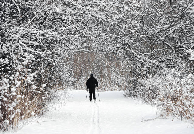 Joe Scharpf cross country skis on a trail after a fresh snowfall in the south chagrin reservation of the Cleveland Metroparks, Thursday, Dec. 28, in Moreland Hills, Ohio. Scharpf said he will ski about 6 miles on the trail.