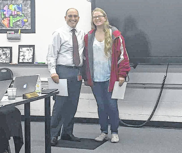 Mike Aurin, left, a teacher at Jonathan Alder High School, and Sandy Moser, right, a junior at Jonathan Alder High School, posed at the board of education meeting on Thursday night. Moser was commended for getting a perfect score of 36 on the ACT.