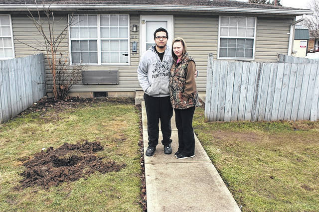 "Tyler Hardin and Judy Schaub stand in front of apartment 10 C Lamplight Court, London — the scene of Monday night's double homicide resulting from a home invasion. The couple's quick action helped save the life of Lamplight resident and shooting victim, Zachary Edmond by calling 911 and transporting him to Madison Health ER by car. Edmond's roommate, William ""Billy"" Benson, was not as fortunate. Benson succumbed to his injuries inflicted by gunshot and was pronounced dead at the scene. Suspected home invader, Justin Coffey, also expired from his wounds at Grant Hospital. A second suspected invader remains unnamed at this time. The hole was dug by investigators to remove a bullet that had passed through Benson's body and into the earth. He was reportedly shot while lying on the ground, the couple said."