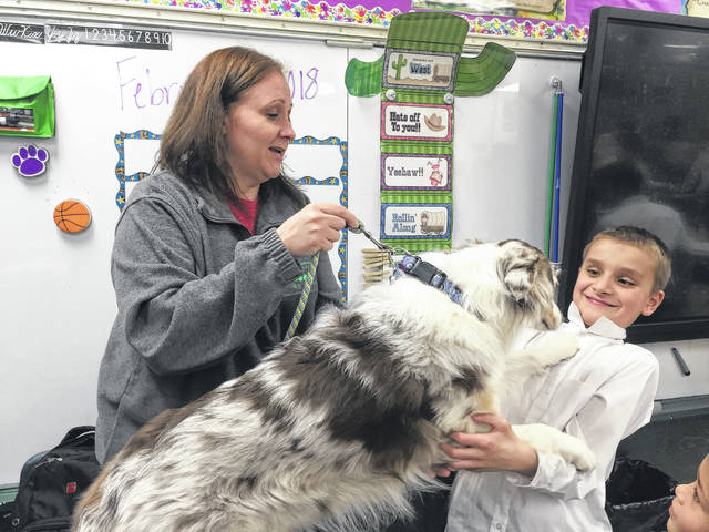 Gus Feliks (right), a third grader at St. Patrick Elementary School, meets Wycked (center), an Australian Shepard, being led by OSU Extension Educator Kirsten Holt (left) on Tuesday. Christen Rinehart's third grade class learned about the 4-H program, dogs and predators/prey.