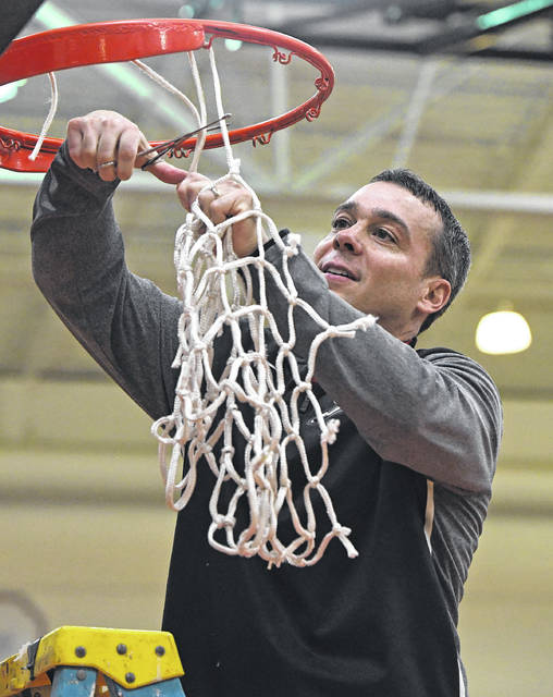 Jonathan Alder boys basketball coach Brent Cahill helps cut down the nets following his Pioneers winning the Central Buckeye Conference Kenton Ridge Division last week.