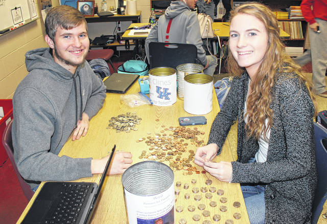 "London High School FFA president, Trent Hart, left, and secretary, Elizabeth Oney, right, count out change for the ""Pennies for Patients"" fundraiser Tuesday. The London FFA chapter is collecting money to donate to the Leukemia and Lymphoma Society."