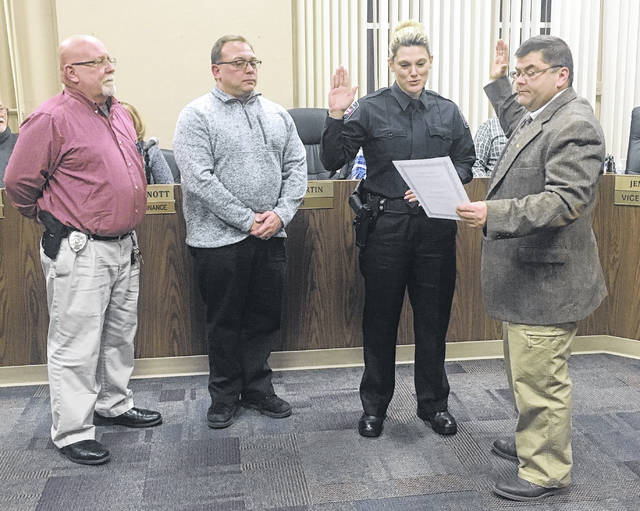 Billie Leevy takes the oath to be the new part-time officer for the West Jefferson Police Department at Monday's village council meeting. From left are: acting chief Lt. Gary McNeal, Timothy Leevy, Billie Leevy and mayor Ray Martin.