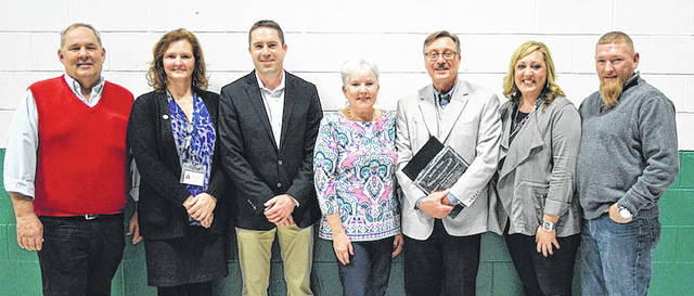 Longtime Madison County Commissioner David Dhume (third from right) was honored for his lifetime commitment to improving the lives of people with disabilities at the recent annual Madison County Board of Developmental Disabilities Appreciation Awards held at Fairhaven School. Surrounded by his family, Brian Dhume, Joanne Dhume and Erin Dhume, he was presented the award by dignitaries including MCBDD Board President Ted Slanker, MCBDD Superintendent Susan Thompson, Sue Hackett (representing her husband, State Sen. Bob Hackett), and State Rep. Bill Dean.