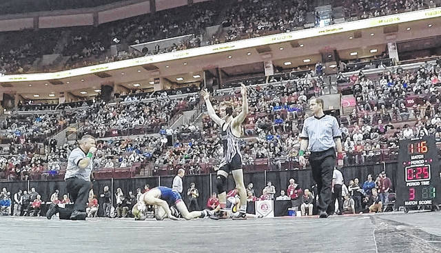 Jonathan Alder senior Jake Johnson (120 pounds) raises his hands in victory following his fifth-place match victory at the OHSAA Division II state tournament at Ohio State University Saturday.