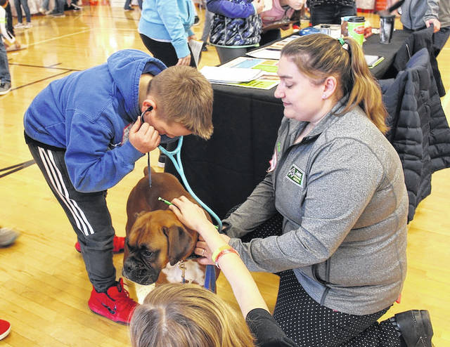Sixth grader, Jace Collins, left, listens to Charlie as Dr. Meagan Boggs of Sheffield Veterinary Hospital holds the leash. London Middle School students got to talk to area businesses and schools on Friday as part of LMS's second Life Fair.