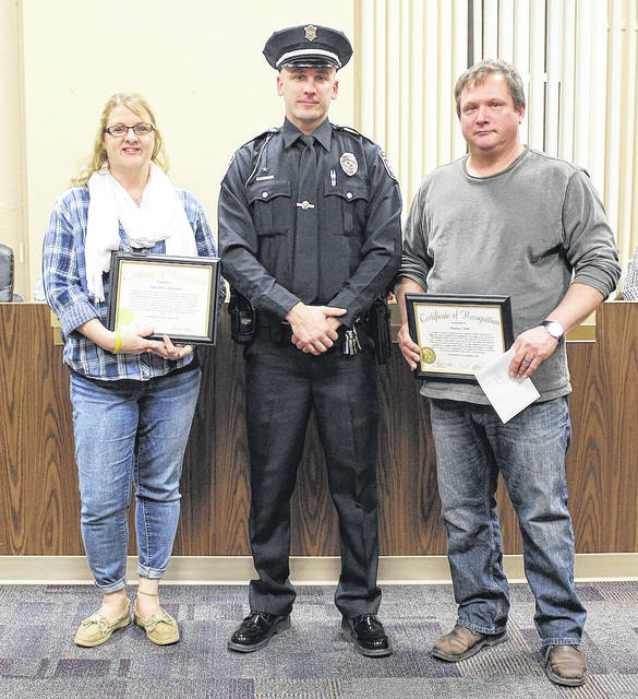 Stephanie Richardson, left, poses with West Jefferson police officer Matt Stevers, center, and Thomas Clark, right, at the West Jefferson Village Council meeting Monday. Ofc. Stevers thanked Richardson and Clark for their assistance in a Jan. 26 incident at Arbors West. The two nursing facility employees were presented with certificates of appreciation from village officials.