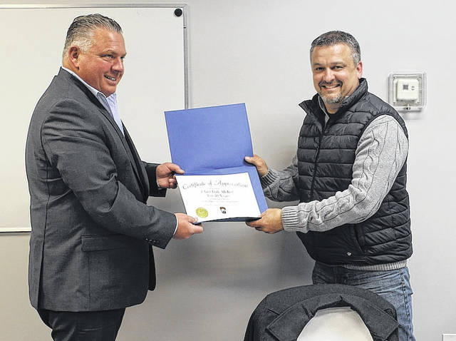 Plain City mayor Darrin Lane, left, presents a certificate of appreciation to police chief Dale McKee at Monday's village council meeting. McKee started working with the village 22 years ago but became a full-time officer in 1998, making this year 20 years in law enforcement in the village.