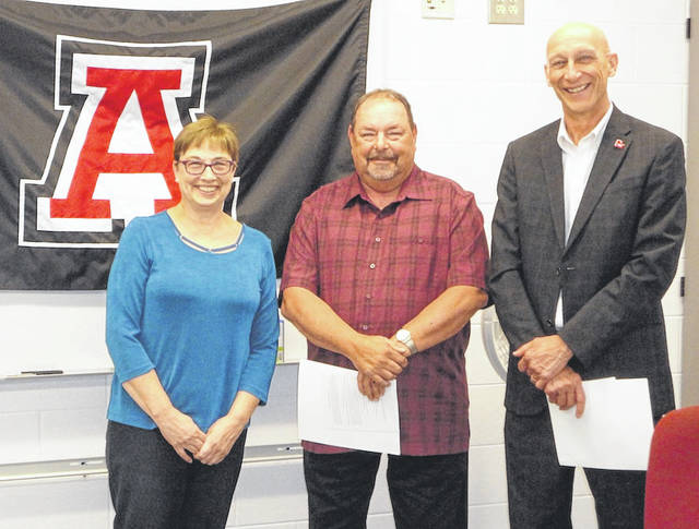 Kim Miller-Smith, left, of the Ohio School Boards Association, presents Jonathan Alder board members Tom Bichsel, center, and Steve Votaw with certificates recognizing their 15 years of service to the school district. The presentation came at the May 14 board meeting.