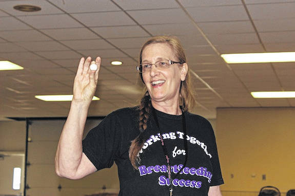 Edie Stroup, Breastfeeding Coordinator/Nutrition Education of Madison County WIC shows attendees the size of a newborn infant's stomach at the Healthy Child & Family Consortium's third annual county-wide baby shower Monday evening. The event, held in the Madison County Fairgrounds Della Selsor building, linked expecting mother with services, items, and information to promote healthy childbirth and child-rearing.