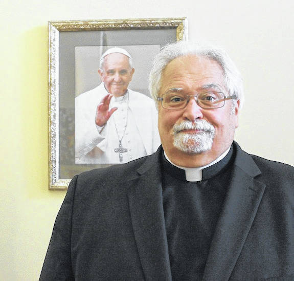 Father William Metzger stands at the entrance of Sts. Simon and Jude Catholic Church in West Jefferson May 18 with a photo of Pope Francis. Metzger will celebrate 40 years in the priesthood on May 27.