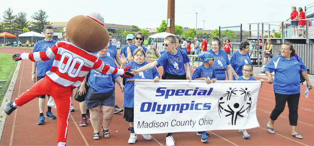 The Madison County Tigers Track and Field team gets welcomed by Brutus Buckeye as they participate in the Opening Ceremonies of the annual Special Olympics Shamrock Games, held recently at Dublin Coffman High School.